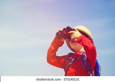 little boy looking through binoculars while travel