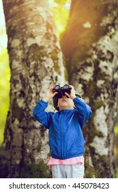 Little boy looking through binoculars in the forest