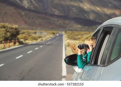 little boy looking through binoculars while travel by car on road