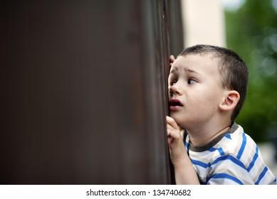 Little boy is looking through a gate