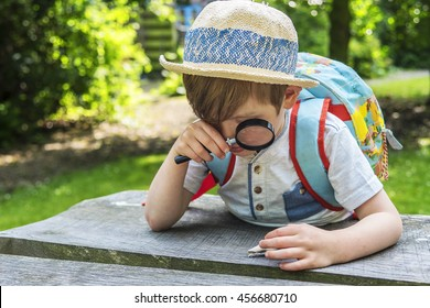 Little boy looking through magnifying glass