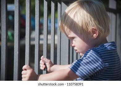 Little boy looking through metal bars