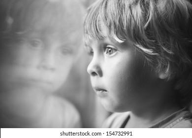Little boy looking through window.