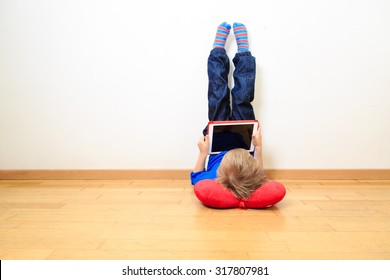 little boy looking at touch pad at home, early learning