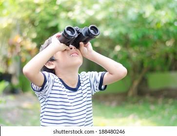 Little boy looking trough a binoculars