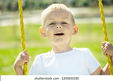 Little boy looks into the camera and enjoys the swings on the playground in the city park on a sunny summer day, close-up
