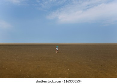 A little boy looks lost in the vastness of the Wadden Sea