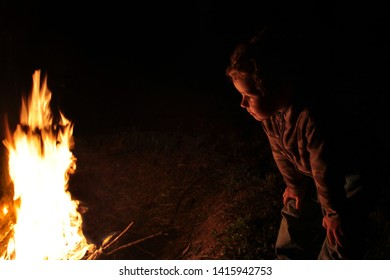 The little boy looks at the night fire