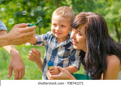 A little boy looks on a soap bubbles. Dad holds his son's hand and teaches him to blow soap bubbles. Mom sits by and looks. Family resting in the park
