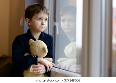 The little boy looks out the window. Rainy Day. Loneliness and waiting concept