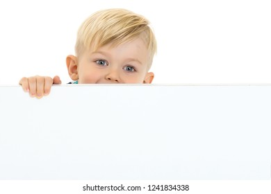 A little boy looks through an empty banner on which you can write any text. The concept of a happy childhood and advertising of children's goods. Isolated on white background.