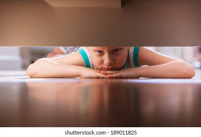 Little boy looks under the bed