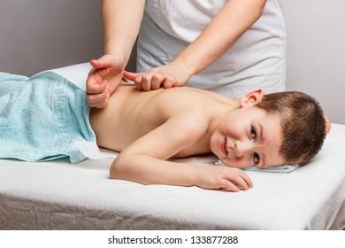 Little boy lying down on a massage bed