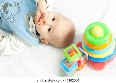 little boy lying down on the bed wis toys