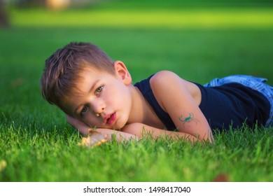 Little boy lying in the grass feeling melancholic