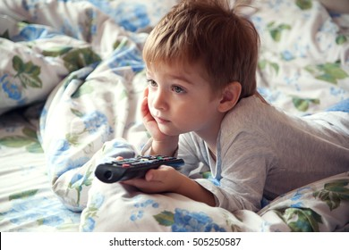 little boy lying on the bed and watching TV