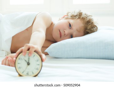 Little boy lying on the bed and stopping alarm clock in morning.