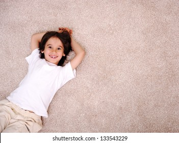 Little boy lying on carpet floor at home and smiling