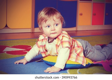 Little boy lying on the colorful carpet in nursery, vintage