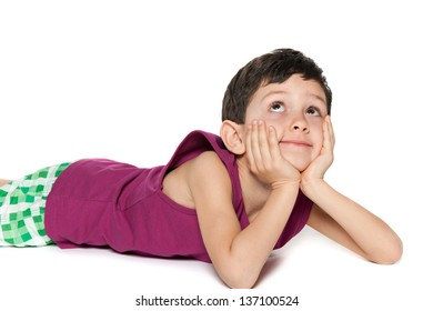 A little boy is lying on the floor on the white background and looking up