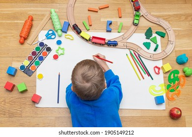 A little boy lying on the floor and painting on paper. Top view photo. Preschool boy play on floor with toys - colored bricks, train, railroad. Child at home on a remote education.