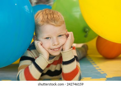 A little boy lying on the floor surrounded by colourful balloons