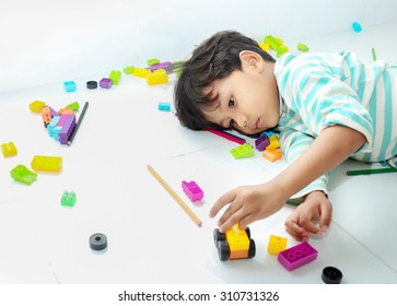 Little boy lying on the floor with toy and he has bored emotion.
