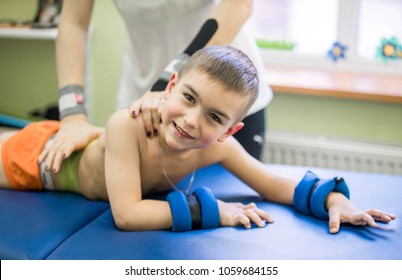 little boy lying on stomach during physiotherapy and look at camera