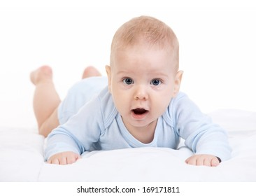Little boy lying on stomach and looking at camera over white background