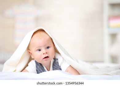 Little boy lying on white bed