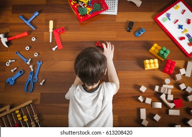 Little boy lying on the wooden floor and playing with colorful toys. Top view