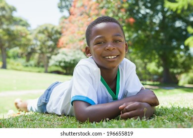 Little boy lying in the park smiling at camera on a sunny day