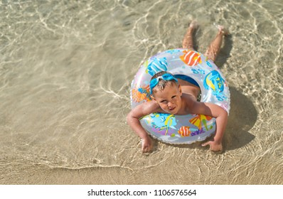 Little boy lying at sandy beach with colorful inflantable ring