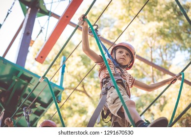 little boy make climbing in the adventure park. Concept of sport life.