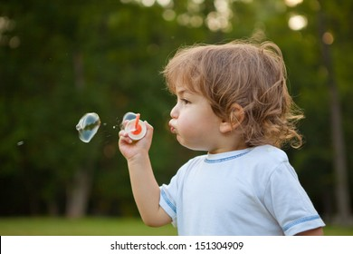 Little boy make a soap bubbles in park