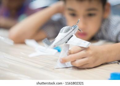 Little boy making an aircraft paper