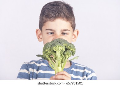 Little boy making a funny face refusing to eat his broccoli