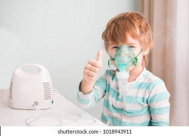 Little boy making inhalation with nebulizer at home.