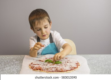Little boy is making pizza, finishing with basil leafs