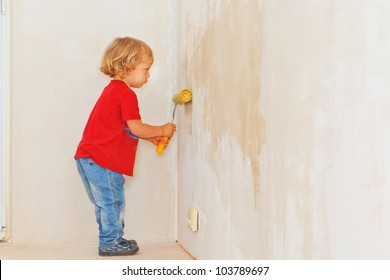 Little boy making renovation, painting the wall