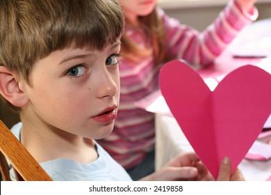little boy making valentine cards