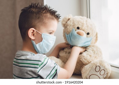 a little boy in a mask sits at home in quarantine and looks out the window in a place with a teddy bear. Prevention of Coronavirus and Covid - 19. Concept