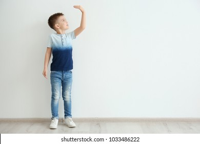 Little boy measuring height near light wall