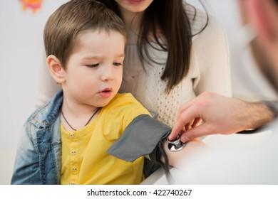 Little boy medical visit - doctor measuring blood pressure of a child