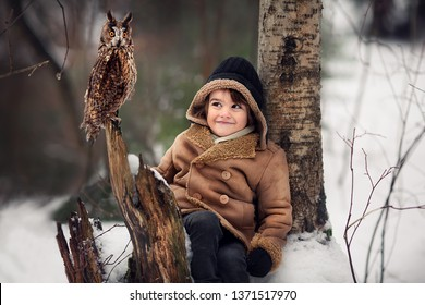 Little boy is meeting an owl in Russian forest in winter. Image with selective focus and toning