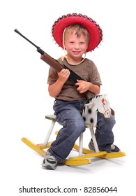 Little boy in mexican hat with gun sitting on a rocking horse.