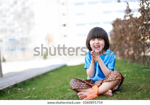 Little boy mixed race Asian-German wearing Thai traditional dress sitting at garden with happy face and water gun celebrating Thai new year or songkran festival