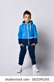 Little boy model wearing sports tracksuit with sweatshirt and pants studio portrait isolated on gray background. Male child posing for camera with hands in pocket. Autumn winter sport children fashion