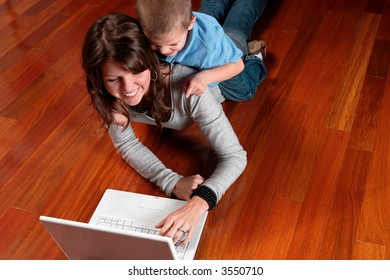 little boy and mom laying on floor looking at a laptop computer