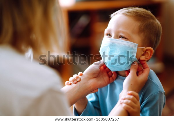 Little boy and mom in medical mask. Mother puts on her baby sterile medical mask. Child, wearing face mask, protect from infection of virus, pandemic, outbreak and epidemic of disease on quarantine.